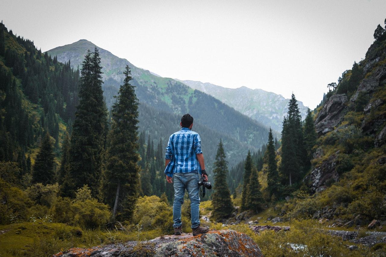 Mand står i mellem to bjerge med et kamera