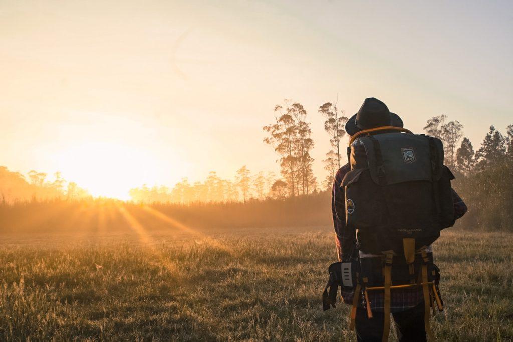 Mand går mod solnedgangen med taske