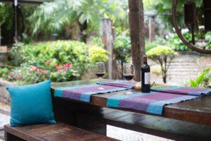 Vinflaske står på terrasse til sommerhus med palmer i baggrunden