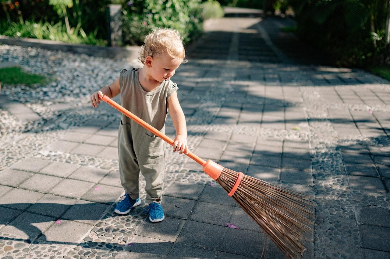 Barn gør rent i haven med kost