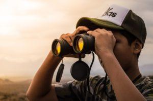 Person kigger i kikkert ud over landskab